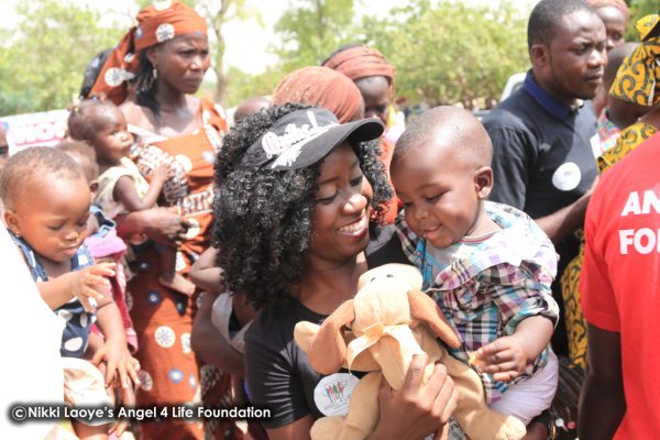 Nikki-Laoye-&-a-cute-baby-all-smiles-as-he-gets-a-toy (1)